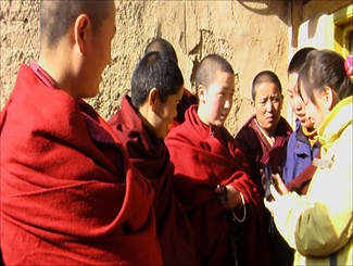 Project Manager, Lumo Tsering of Shem Women's Group is explaining to the nuns how to use and charge the solar flashlights.